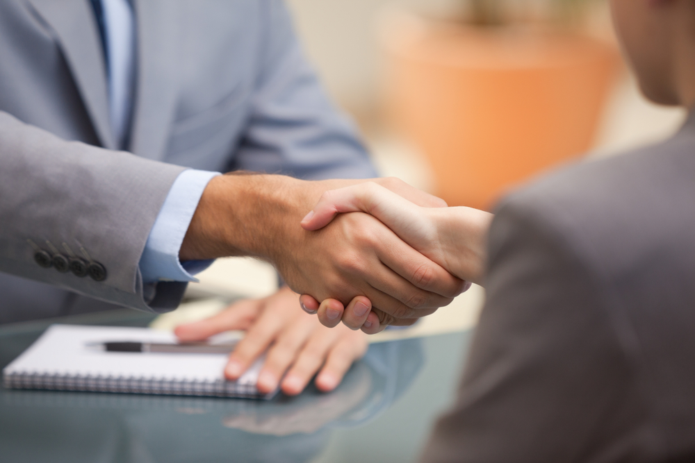 Two Businesspeople shaking hands indoors